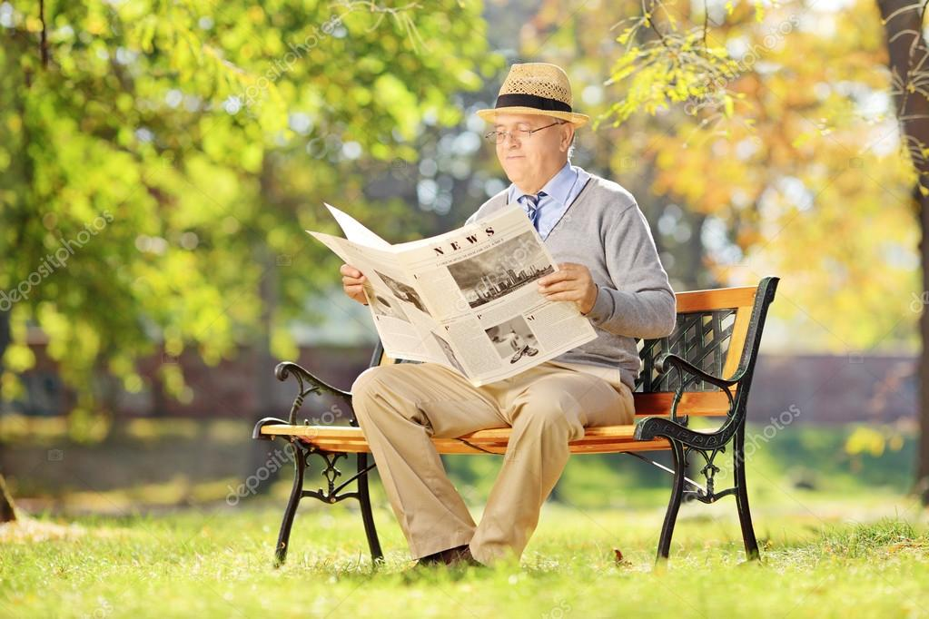 Senior man reading a newspaper in autumn
