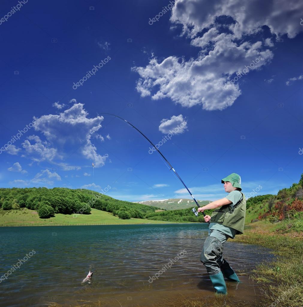 Fisherman fishing on lake