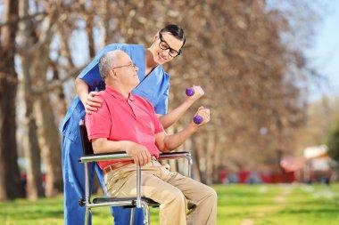 Male nurse and senior lifting dumbbells