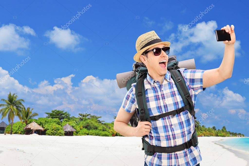 Tourist taking selfie at beach