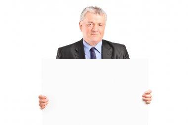 Mature businessman holding blank poster