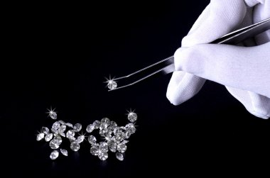 Beautiful shining crystal (diamond) in the tweezers