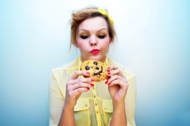 Young attractive woman with red hair and a yellow bow headband wearing a yellow chiffon blouse is holding a smiling chocolate chip cookie and looking at it with an indecisive look.