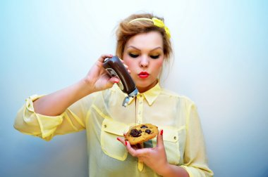 Young stylish woman with red hair and a yellow bow headband wearing red lipstick and a yellow chiffon blouse is pouring chocolate sauce over chocolate chip cookie.