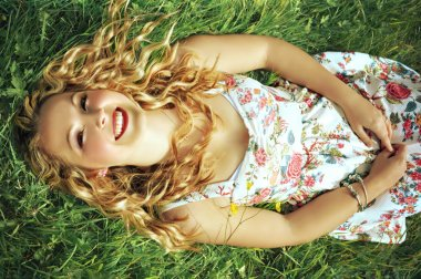 Happy young blonde woman with curly hair wearing red lipstick and a small flower print summer dress is lying on green grass and smiling.