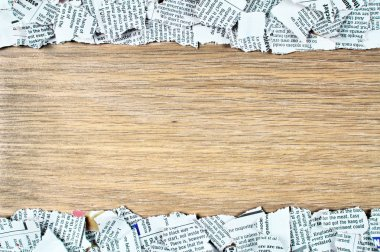 Blank wooden surface covered with shredded newspaper pieces on top and bottom, leaving the middle part clear.