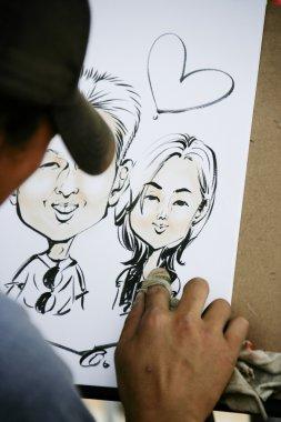 Street artist draws a portrait of people