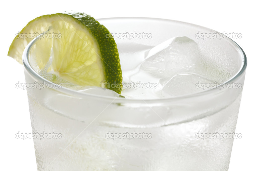 Glass of water with floating ice cubes and lime slice — Stock ...