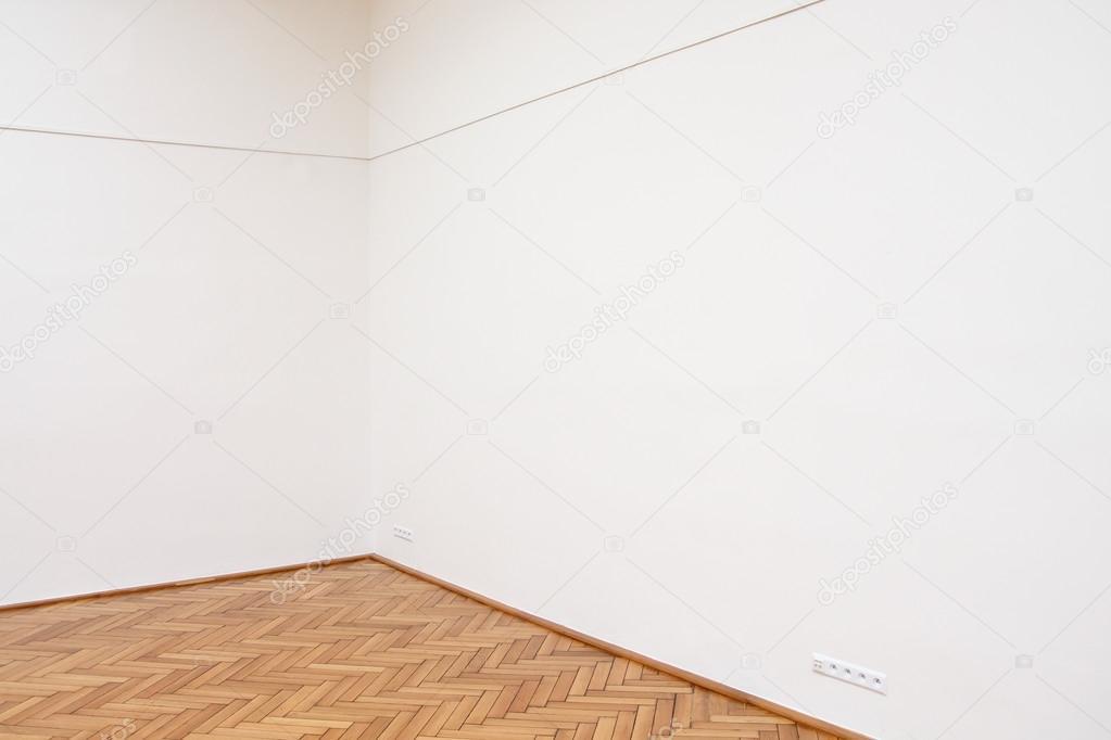 Angolo di una grande parete bianca con piastrelle del pavimento in