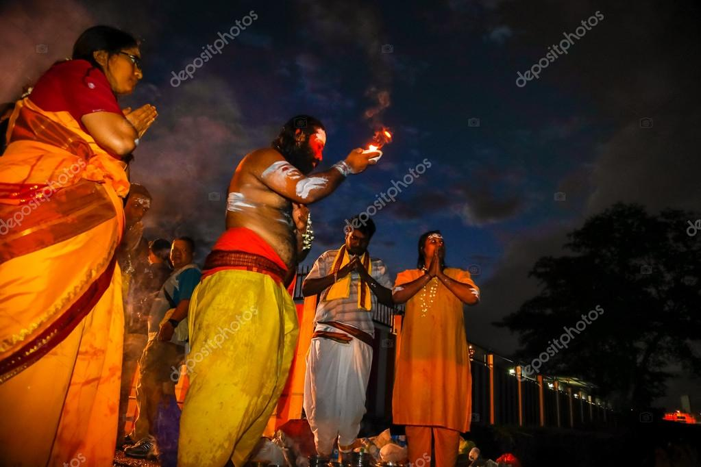 KUALA LUMPUR - JANUARY 27: A Hindu priest performs prayer for Lord Muruga with a family at dawn at the Batu caves temple in Malaysia on January 27, 2013 during the Thaipusam festival.