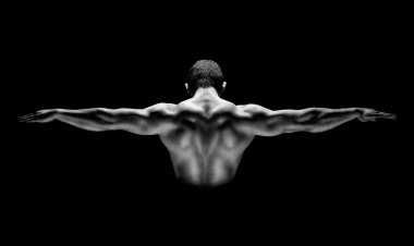 Rear view of healthy muscular man with his arms stretched out isolated on black background
