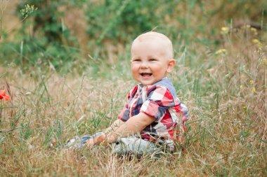 Fashion baby boy walking in grass