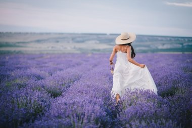 Beautiful young woman running in a lavender field