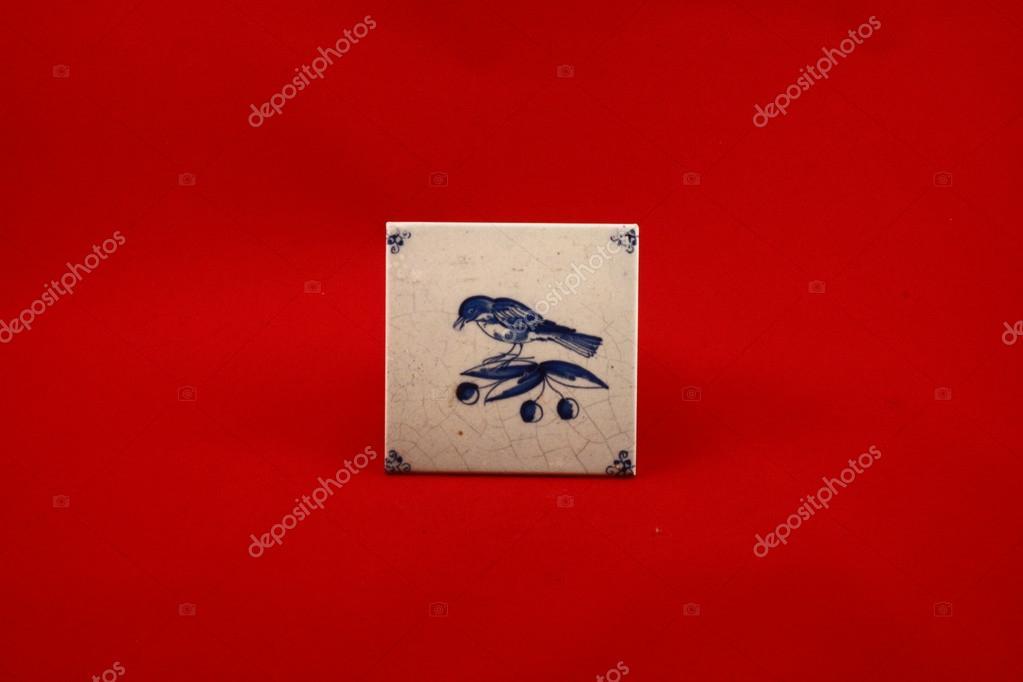 Tegel Delfts Blauw : Delfts blauwe tegel met vogel en kersen met een rode achtergrond