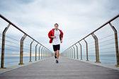 Fotografia uomo giovane atleta in t-shirt bianca e sport corre una giacca a vento rossa spiaggia molo