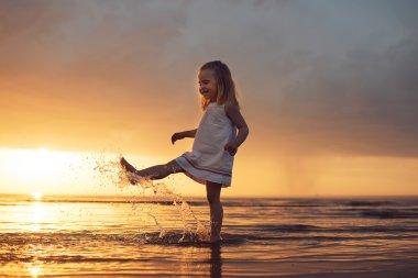 happy little girl running on the beach
