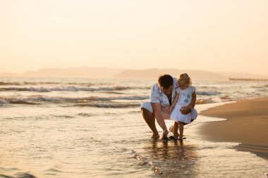 Happy father playing with his daughter by the seaside at sunset,