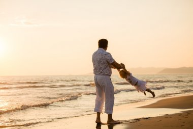 Happy father with his little child by the seaside at sunset, sum