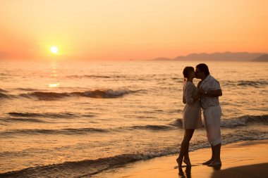 Man and woman kissing at beach with sunset in the background, It