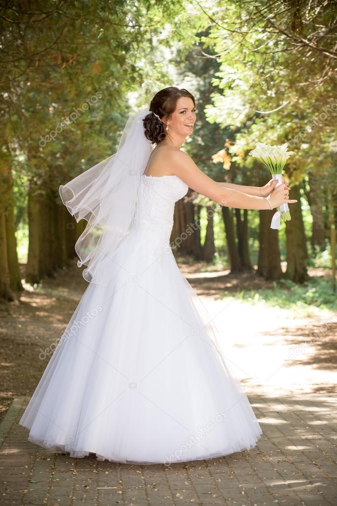 schöne Braut im Hochzeitskleid und Brautstrauss, freudig frisch ...