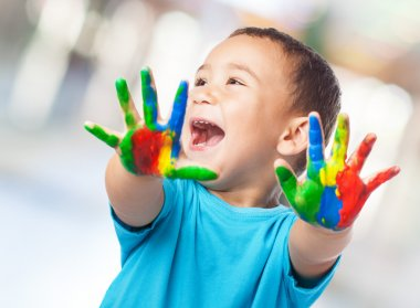 Kid having fun with hands paint