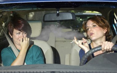 Woman smoking while driving inside the car