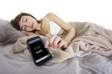 Female snoozing modern cell phone alarm clock