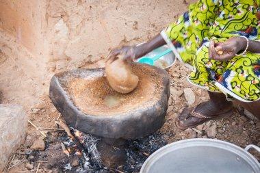 Dogon woman preparing food using peanut paste, Mali, Africa.