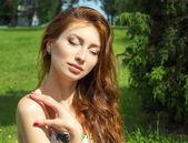 krásná mladá dívka s rudými vlasy velké plné rty se uvolnil, spočívající v parku
