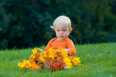 Funny baby with pumpkins halloween