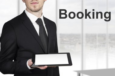 Businessman holding tablet pc booking