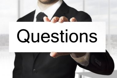 businessman holding sign questions
