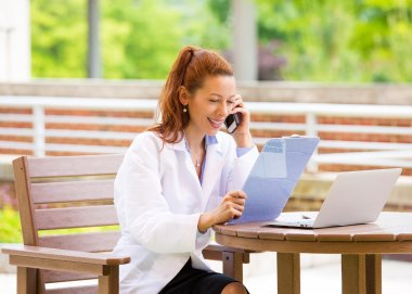 Female doctor on a phone, outdoors
