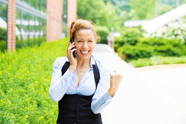 Business woman on a phone, outdoors celebrating success