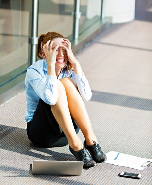 Stressed business woman sitting on a floor