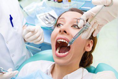 Female patient in dentist office getting anesthesia before tooth