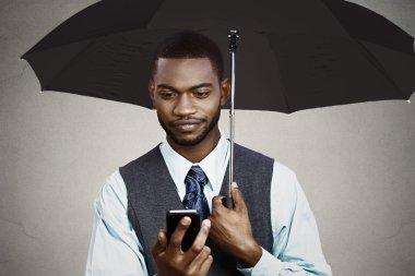 Businessman texting under umbrella