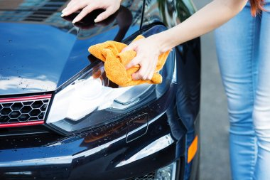 Woman cleaning , drying car with microfiber cloth