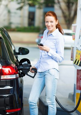 Woman at gas station, filling up her car