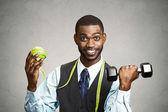 Fotografie Man holding green apple and dumbbell