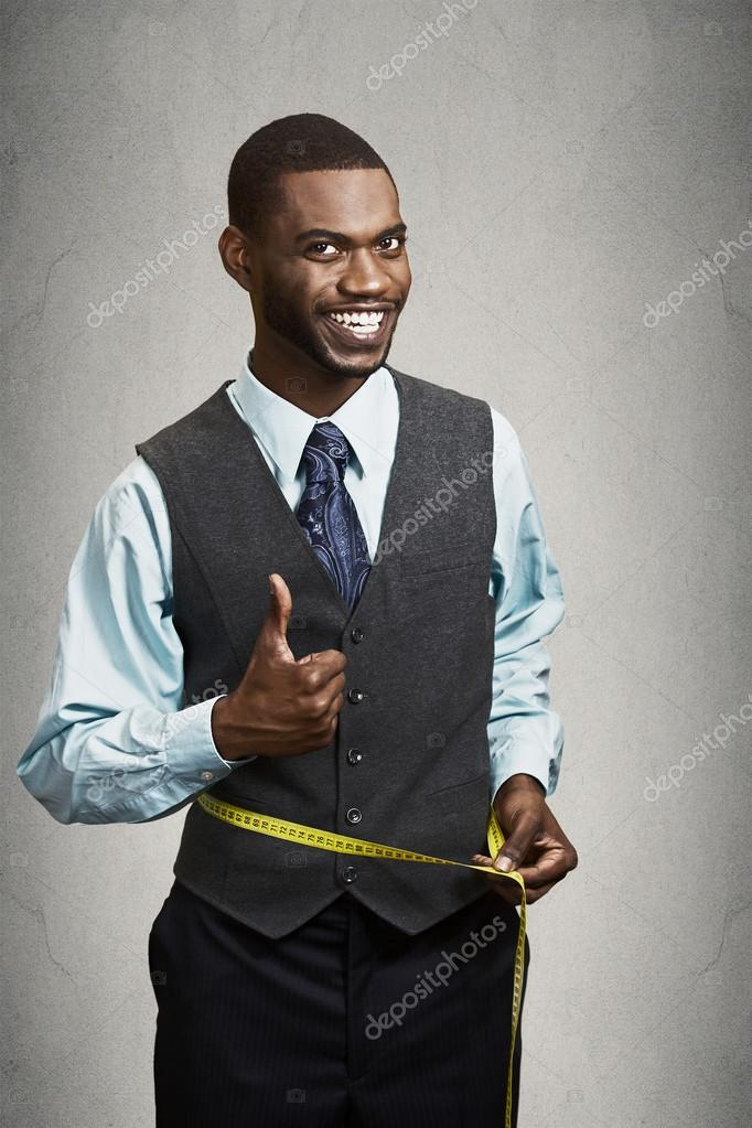 Happy man measuring his waist with tape