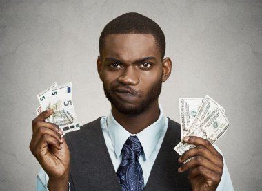 Confused businessman holding dollar, euro bills