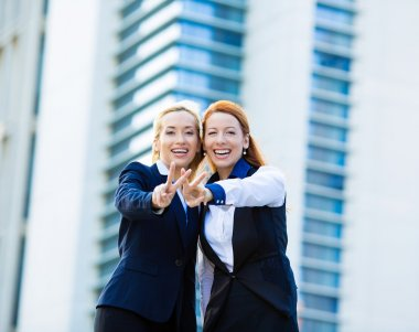 Two excited business women, friends giving victory sign, gesture