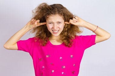 Unhappy stressed girl covering ears from loud noise