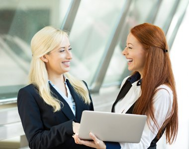 Happy businesswomen smiling, discussing a deal, holding computer