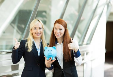 Portrait two happy business women holding piggy bank giving thum