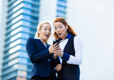 Surprised business women looking at smart phone, receiving unexp