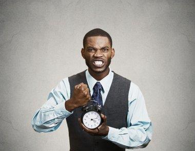 Portrait of demanding corporate boss holding alarm clock screami