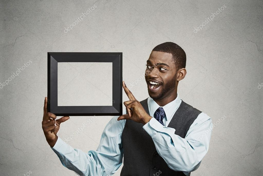 Happy businessman holding empty picture frame