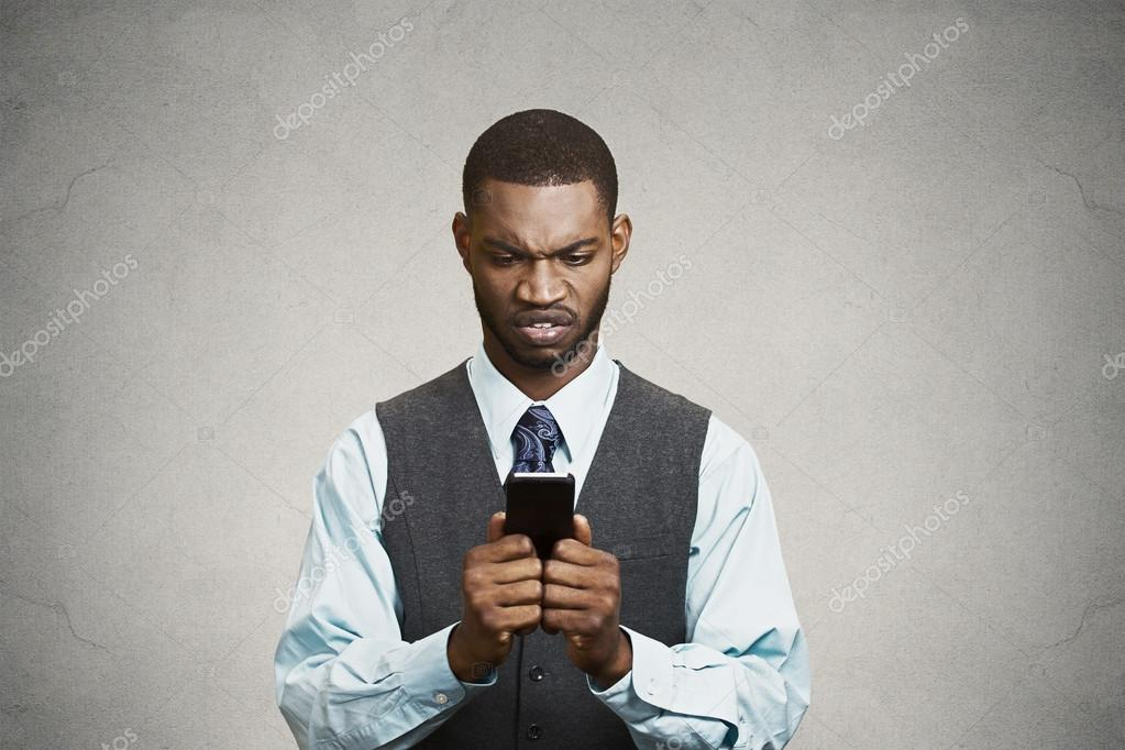 Angry executive holding smart phone, reading e-mail
